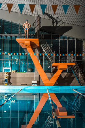 swimmer standing on diving platform ready to jump at swimming pool