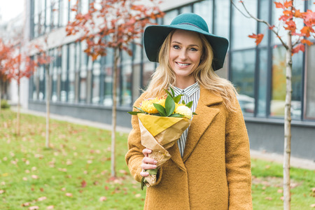 attractive stylish woman in yellow coat and felt hat holding bouquet