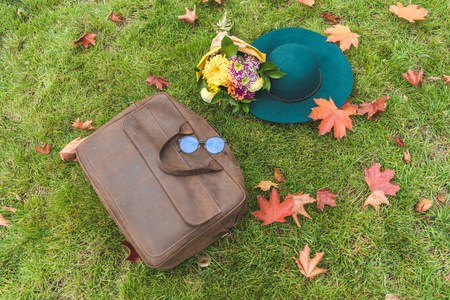 top view of felt hat and bouquet, leather bag and eyeglasses on green lawn with foliage