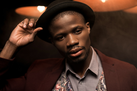 portrait of handsome fashionable african american man in hat in dark smoky room with lamps