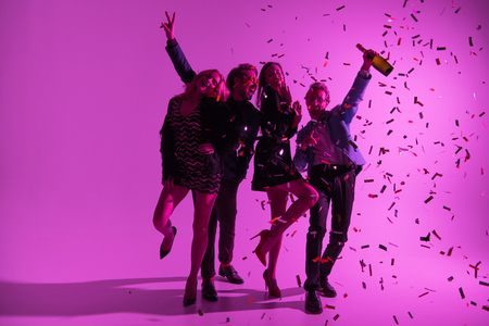 silhouette of stylish friends having fun with champagne bottle and confetti, on pink