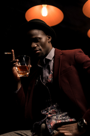 handsome fashionable african american man in hat smoking cigar and drinking whiskey in dark room with lamps Zdjęcie Seryjne