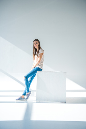 full length view of beautiful young woman smiling at camera while sitting on grey