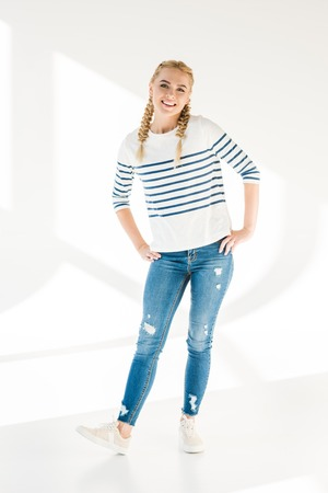 full length view of happy blonde girl smiling at camera on grey
