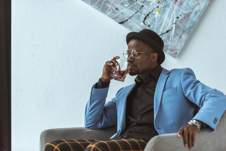 stylish african american man in hat and blue jacket sitting in armchair and drinking whiskey Reklamní fotografie