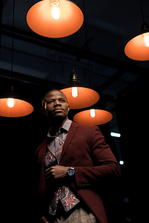 stylish elegant african american man in jacket standing in dark room with lamps