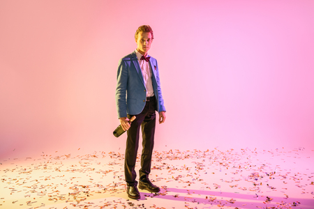 young handsome man with bottle of champagne standing on confetti, on pink Banque d'images - 102661159