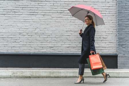 beautiful woman with umbrella and shopping bags walking in city Stock Photo