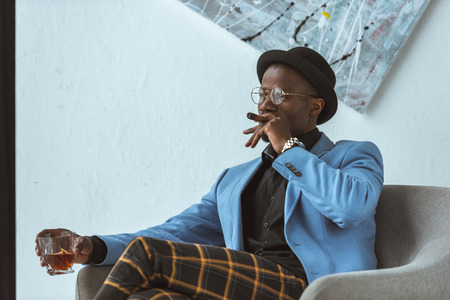 handsome stylish african american man in hat, checkered pants and blue jacket with cigar and glass of whiskey sitting in armchair in modern office Zdjęcie Seryjne