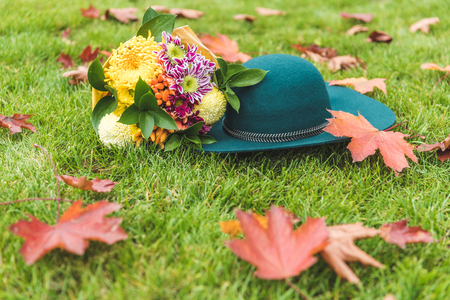 felt hat and bouquet of flowers on green grass with foliage
