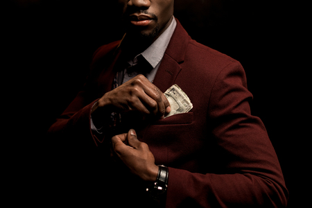 cropped view of rich african american man putting dollar banknotes into pocket isolated on black