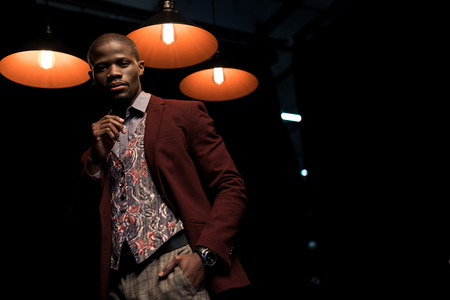 stylish elegant african american man in jacket isolated on black with lamps