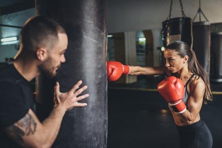 Apuesto joven entrenador sosteniendo saco de boxeo mientras entrenamiento de boxeadora
