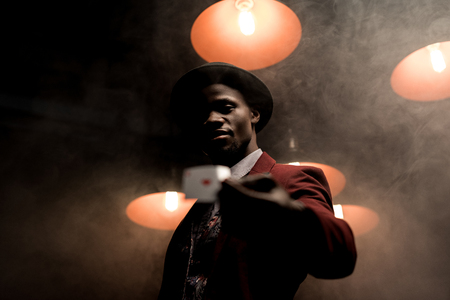 handsome lucky african american man with playing card in hands in dark smoky room with lamps