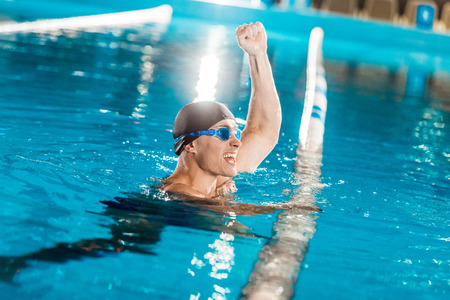 handsome winning muscular swimmer in competition swimming pool