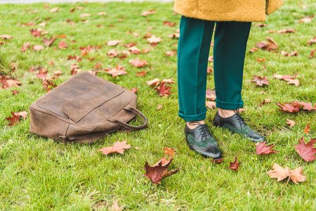 low section of fashionable woman in green pants and brogue shoes standing on lawn with autumn foliage and leather bag Stock Photo