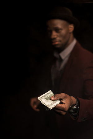 selective focus of african american man holding dollar banknotes,  isolated on black