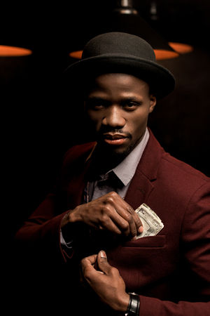 handsome rich african american man in hat putting dollar banknotes into pocket