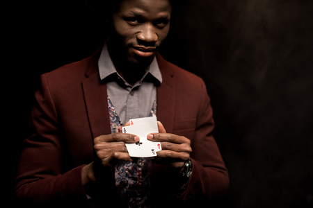 handsome elegant african american man with aces in hands,  isolated on black