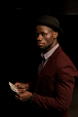 handsome rich african american man in hat holding dollar banknotes, isolated on black Stock Photo