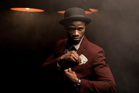 handsome rich african american man in hat holding dollar banknotes in smoky room with lamps Stock Photo