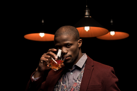 stylish elegant african american man drinking whiskey in dark room with lamps Stock Photo