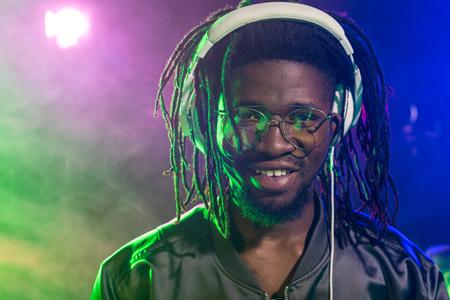 professional african american DJ in headphones in nightclub