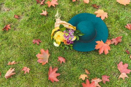 top view of felt hat and bouquet of flowers on green lawn with foliage 版權商用圖片
