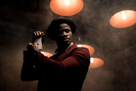 handsome elegant african american man with playing card in hands in dark room with lamps