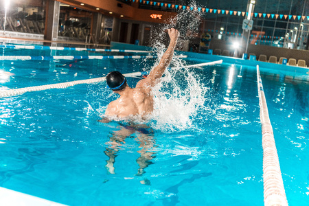 back view of winning swimmer gesturing in competition swimming pool