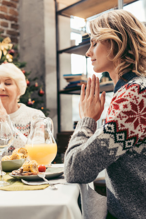 religious senior mother and daughter praying on christmas before dinner