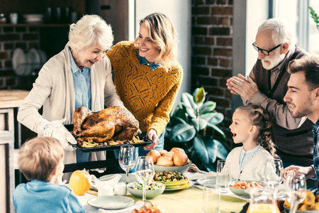 beautiful grandmother carrying turkey for family on thanksgiving dinner Фото со стока - 102661609
