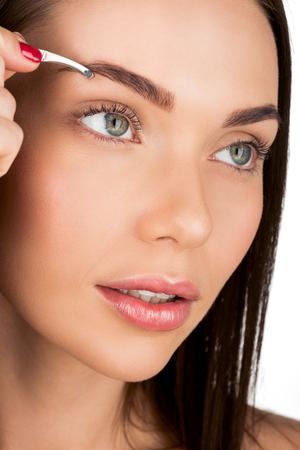 young beautiful woman doing eyebrow correction isolated on white