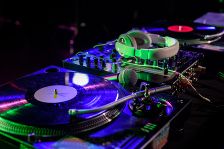 close up view of sound mixer with vinyl and headphones in nightclub