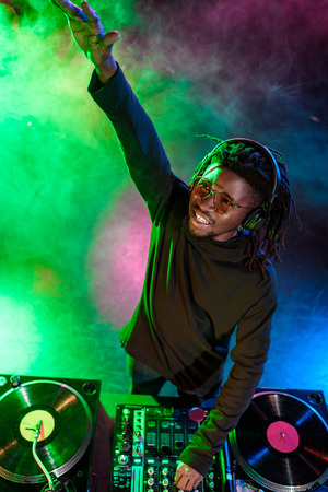 professional african american club DJ in headphones with sound mixer on concert  Stock Photo