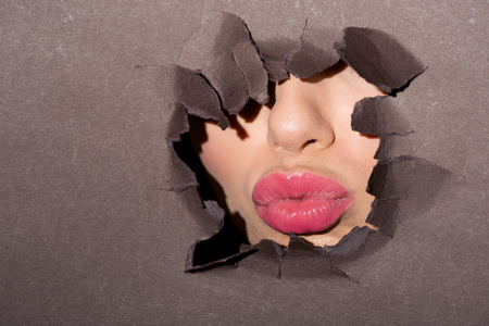 pink lips of woman peeking out of ragged hole in dark paper Stock Photo