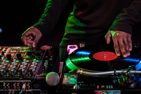 cropped view of DJ hands with sound mixer and vinyl