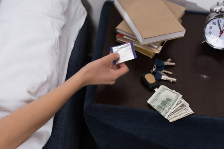 cropped shot of woman taking condom from nightstand
