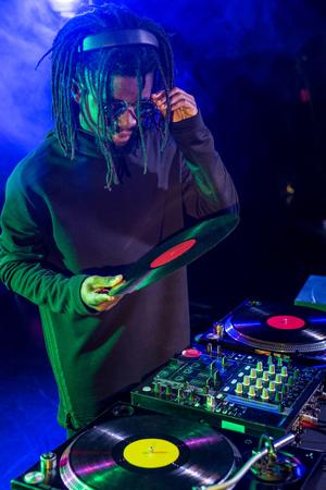 professional african american club DJ with vinyl in nightclub