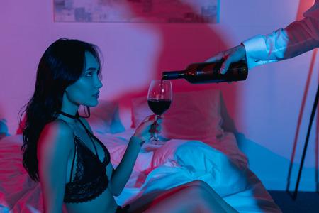 man pouring wine for beautiful girlfriend in dark bedroom