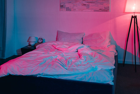 modern empty bedroom at night with red and blue light Banco de Imagens