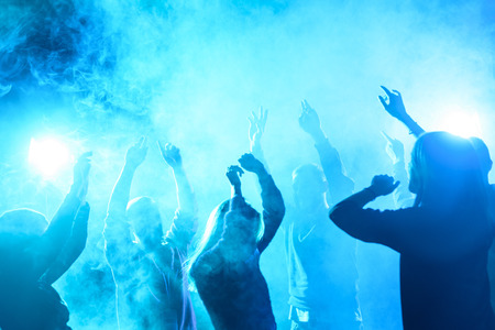 people dancing in nightclub with blue back light