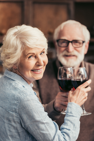 senior couple clinking glasses of red wine and looking at camera