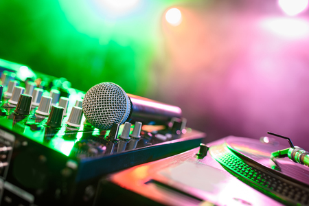 close up view of sound mixer with microphone in nightclub with backlit