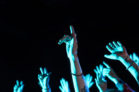 cropped view of hands on party in nightclub with blue back light Stock Photo