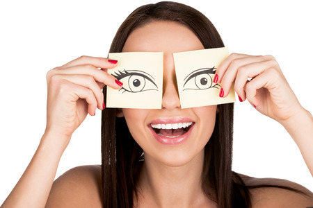 woman covering eyes with cartoons style drawn eyes on stickers isolated on white
