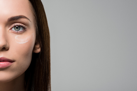 close-up portrait of young woman with moisturizing cream on face isolated on grey Foto de archivo - 102661763