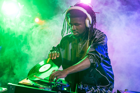 professional african american DJ in headphones with sound mixer in nightclub Stock Photo - 102661767