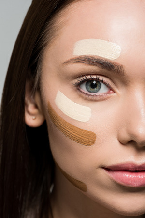 young beautiful woman with tonal foundation on face isolated on grey