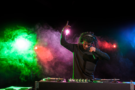 professional african american club DJ in headphones with microphone in nightclub